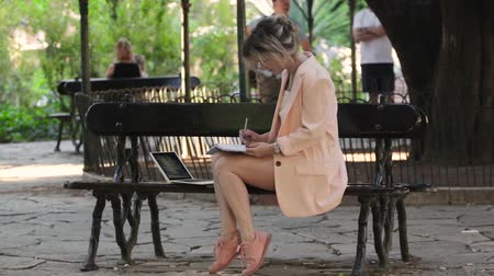 mês : Attractive blonde white woman working freelance with laptop and smartphone in park at sunny day Stock Footage