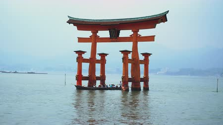 zoom in on boat passing under the famous floating torii in Miyajima Stock Footage
