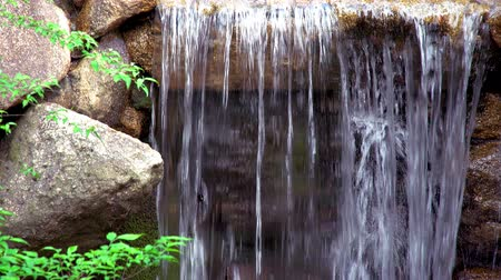 closeup view of a small waterfall among rocks, tilt down shot Stock Footage