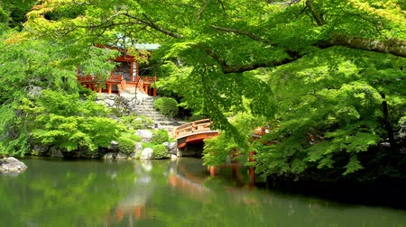 Daigo-ji temple, red bridge and lush garden reflecting in a fish pond