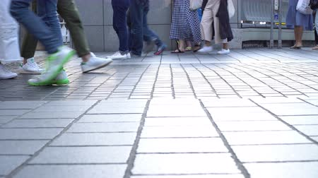 pedestrians walking in a tiled up street, low angle shot