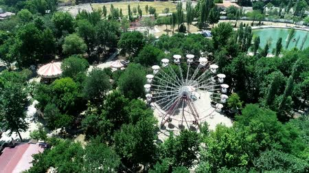 Attraction ferris wheel in the green summer park Stock mozgókép