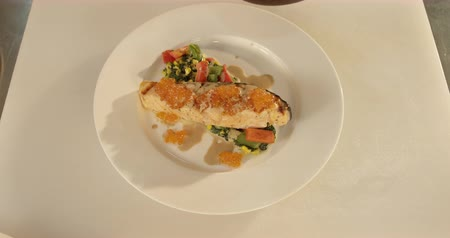Cooking: serving of fish stake with veggies and caviar close up