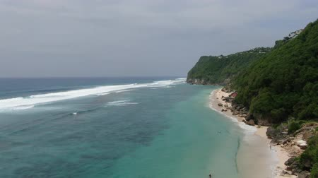 Surf on the sandy ocean coast of Bali on a cloudy day. Indonesia, Drone. Wideo