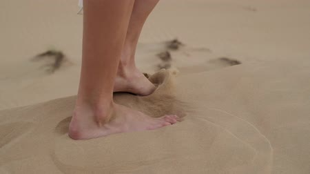 voetstappen : A brunette barefoot in a white dress fluttering in the wind walks along the desert sand. Slow motion.