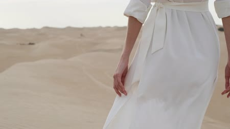 A brunette barefoot in a white dress fluttering in the wind walks along the desert sand. Slow motion.
