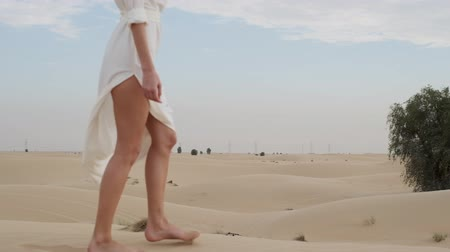 chique : A brunette barefoot in a white dress fluttering in the wind walks along the desert sand. Slow motion.