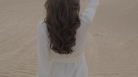 elegante : A brunette barefoot in a white dress fluttering in the wind walks along the desert sand. Slow motion.
