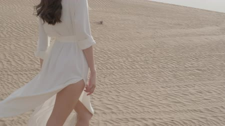 lidské tělo : A brunette barefoot in a white dress fluttering in the wind walks along the desert sand. Slow motion.