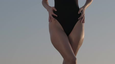 A brunette in a black swimsuit stands barefoot on the sand dune in the desert. Slow motion. Wideo
