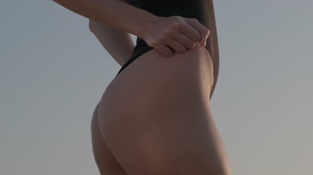 modelka : A brunette in a black swimsuit stands barefoot on the sand dune in the desert. Slow motion. Wideo