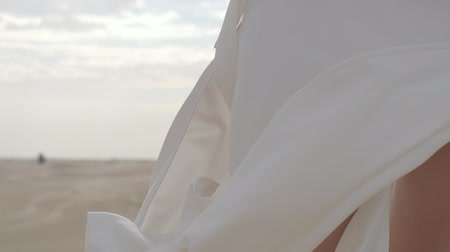 kleider : The rays of the sun through the hands of a girl in a fluttering white dress standing on the sand. Slow motion.