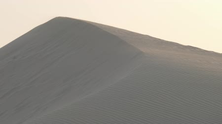 Sand dunes in the desert of Dubai during the wind. Slow motion