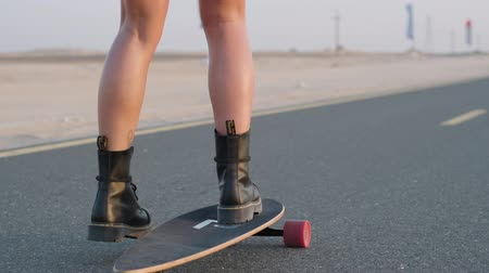 bruslení : Girl rides on a skateboard on a desert road among the sand dunes in Dubai. Close up, Slow motion. Dostupné videozáznamy