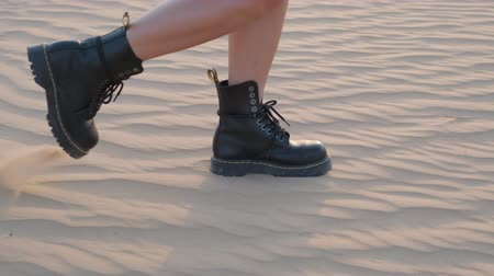 modelka : A girl with a skateboard walks along the sand dunes in the desert in Dubai. Slow motion.
