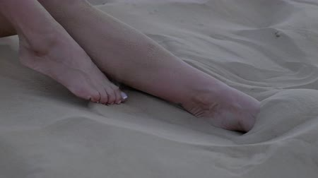 modelka : Feet of a girl lying on a sand dune in the desert of Dubai. Slow motion, close up. Wideo