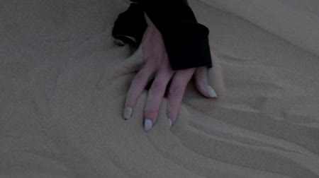 modelka : Hand of a girl lying on a sand dune in the desert of Dubai. Slow motion, close up.