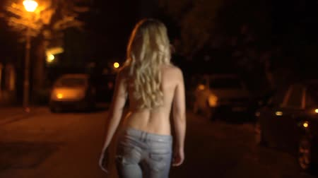 sokak lâmbası direği : Blonde girl with wavy hair, dressed only in jeans, walking alone at night on an empty street. Stok Video