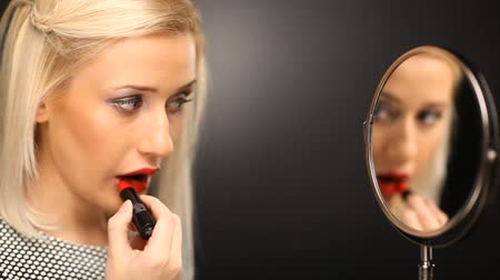ruj : Blonde girl putting on red lipstick in the mirror Stok Video