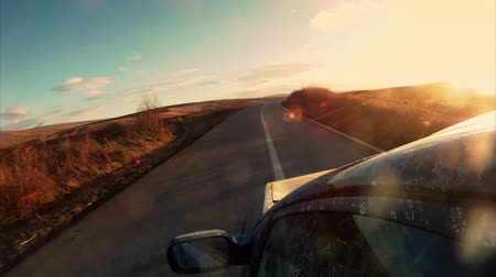 kopec : Driving towards the sunset along an open road with hills in the distance. Dostupné videozáznamy