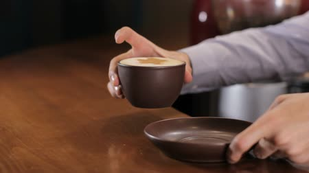 porce : Bartender serves coffee cappuccino on wooden bar counter. Girl picks it up