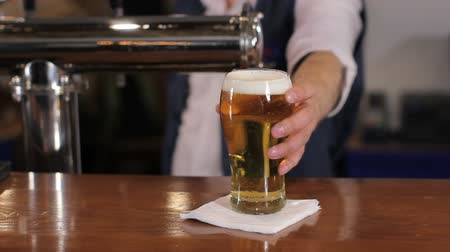 cerveja : Bartender pouring glass of draft beer, putting it on the bar counter and leaving. Medium shot Vídeos