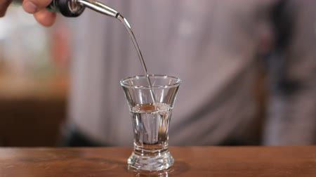 close up shot : Bartender slowly pours one shot of alcohol. Close up