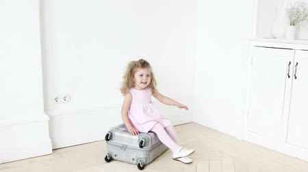 álmodozó : Playful girl sitting on luggage