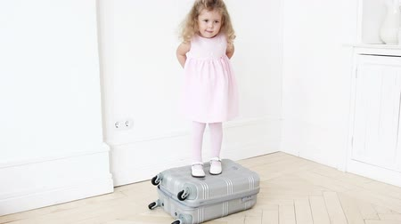 álmodozó : Playful girl standing on luggage