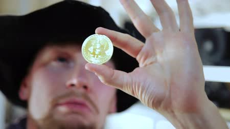mining farm : Man looking And checks the coin for authenticity Stock Footage
