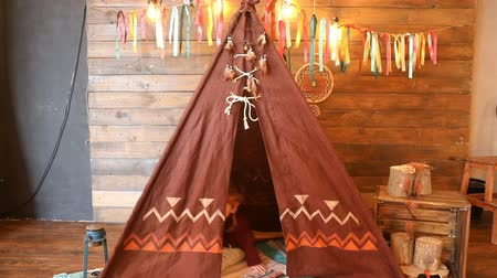 nativo americano : Kid playing in wigwam at home