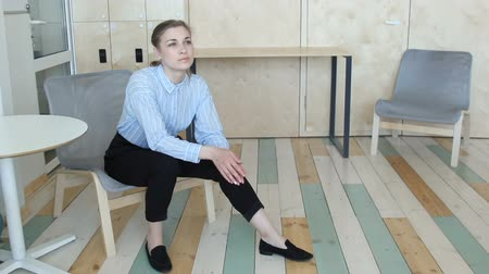 Young woman sitting on chair in office