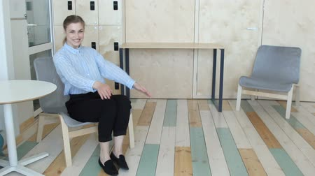 Young woman sitting on chair and invites to come in Стоковые видеозаписи