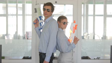 Office workers standing with water pistols in office