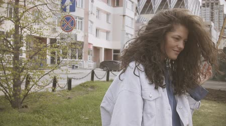 multinational : Curly haired girl in denim jacket and blue hoodie on the street.