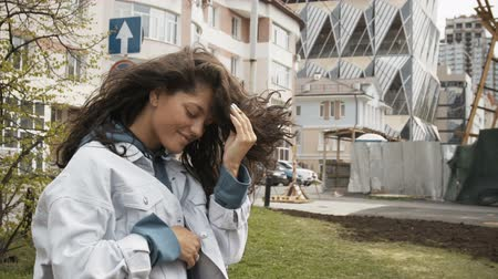 kıvırcık saçlar : Curly haired girl in denim jacket and blue hoodie on the street.