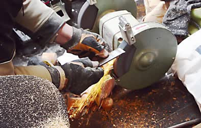 grindstone : The worker sharpens the tool on an electric grinding wheel