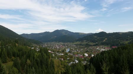 view of Verkhovyna settlement in the Carpathian mountains Ukraine, tilt from the settlement at the foot of the mountain to pine trees (top view). tilt from top to bottom. Full HD, no sound. Стоковые видеозаписи