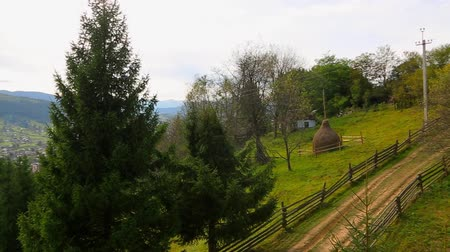 view of the settlement Verkhovyna in the mountains of the Carpathians Ukraine, pan of the mountain road to the settlement at the foot of the mountain. from right to left. Full HD, no sound. Стоковые видеозаписи