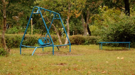 moving empty swing. Childrens blue chain swing. one swing moves with a small amplitude, the second almost without movement. autumn. full hd, no sound.