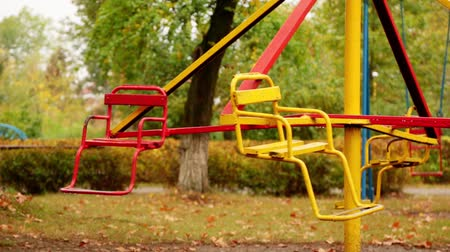 motion of an empty childrens carousel. the carousel moves at an average speed counterclockwise. autumn. full hd, no sound.