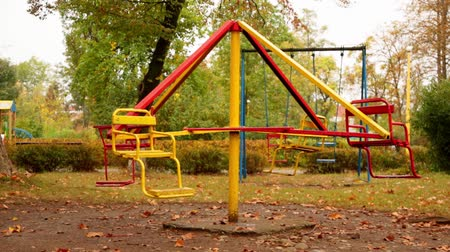 motion of an empty childrens carousel. the carousel moves at a minimum speed counterclockwise and stops. autumn. full hd, no sound.