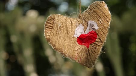 a heart woven from a rope sways in the wind against the background of a wedding decoration made of white balls and ribbons. close-up, full hd, no sound. Стоковые видеозаписи