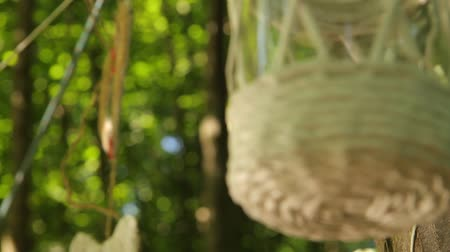 a close-up of a decorated glass jar swaying from the wind, a change focus to a heart braided from a rope hanging in the background, wedding decor. full hd, no sound.