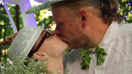 happy pastafarian couple kisses with colanders on their heads during their wedding in the forest. full hd, no sound. Стоковые видеозаписи