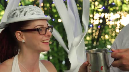 a young pastafarian girl with a colander on her head picks up an iron grit and drinks from it