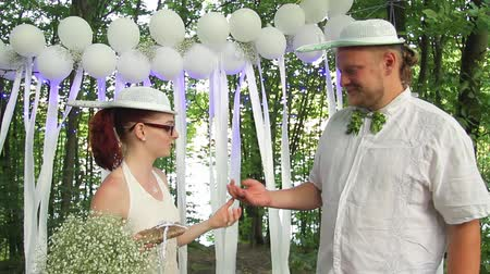 happy pastafarian couple, the bride puts a wedding ring on the finger of the groom during their wedding in the forest. full hd, no sound. Стоковые видеозаписи