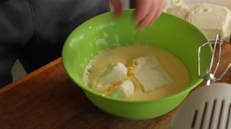 the men puts the cottage cheese from the plate by placing it in the egg mass located in the green bowl. close-up. Wideo