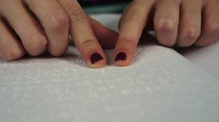 persiana : Young blind woman reading text in braille language