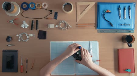 inventing : Top view technician man is working on hard disk drive on his desk full of equipment